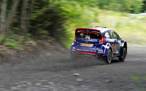 The M-Sport Ford Fiesta R5 powers out of a right-left chicane with all four wheels spitting gravel.