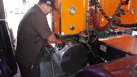 """Klumpp wrangles the diesel pump. He spent $607.96 on fuel at our one stop. """"A complete fillup would be over a thousand,"""" he said."""