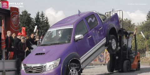 Yes, that is a purple Toyota Hilux about to get powerslammed by a forklift.