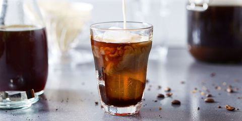 pouring milk creamer into glass of homemade cold brew coffee in kitchen