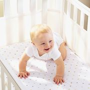 baby toddler smiling in white crib with breathable fabric crib bumpers on the sides