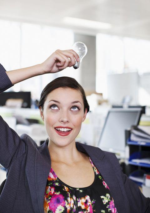 Smiling businesswoman holding light bulb overhead in office