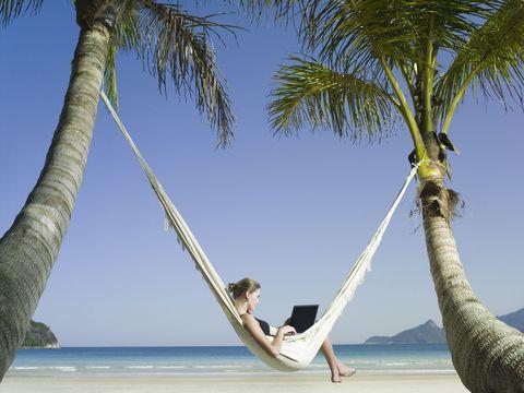 Ragazza seduta su un'amaca in spiaggia con il computer portatile