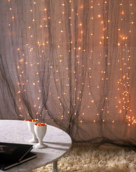 Unisci più fili di luci di Natale per creare una tenda di luce impalpabile, puoi sovrapporla alle tende della sala oppure crearne una nuova su una parete vuota della stanza