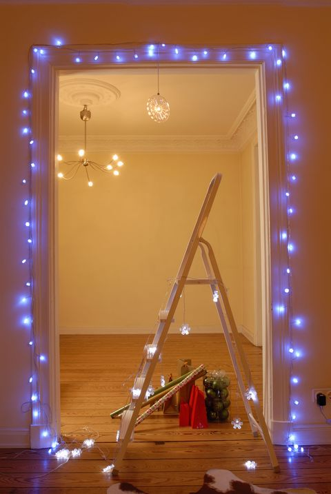 Aiutati con una scala e fai scorrere lungo gli stipiti delle porte le luci di Natale