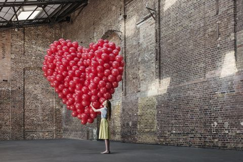 Woman in warehouse with heart made of balloons
