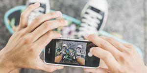 Ragazzo che fotografa i suoi piedi sullo skate con lo smartphone