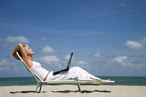 Ragazza in spiaggia con il laptop