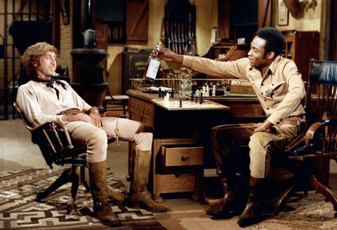 Full shot of Cleavon Little as Bart offering whiskey bottle for Gene Wilder as Jim, both seated in sheriff's office.PHOTOGRAPHS TO BE USED SOLELY FOR ADVERTISING, PROMOTION, PUBLICITY OR REVIEWS OF THIS SPECIFIC MOTION PICTURE AND TO REMAIN THE PROPERTY OF THE STUDIO. NOT FOR SALE OR REDISTRIBUTION. ALL RIGHTS RESERVED.