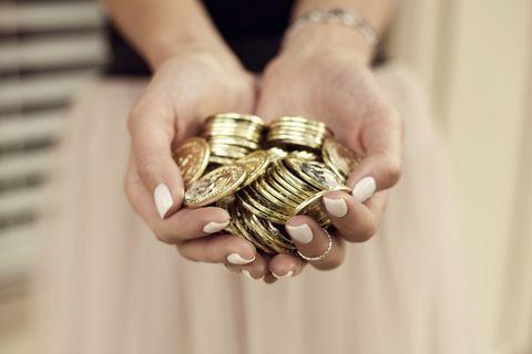 Un mucchio di monete d'oro tra le mani di una ragazza