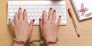 Ragazza con le mani ammanettate alla tastiera del computer