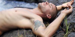 un ragazzo steso a terra con un tatuaggio sul braccio