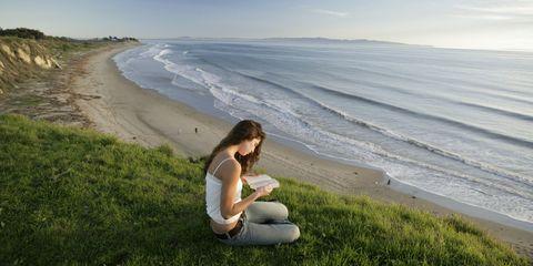 Ragazza che legge un libro al mare