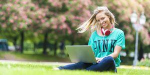 Una ragazza studia e lavora al computer in un parco durante l'estate