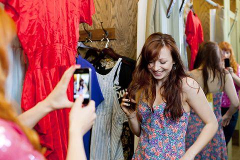 657bb7ba275a Due ragazze provano vestiti in un negozio e si fanno i selfie