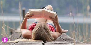 Una ragazza sdraiata sul ponte di un lago legge un libro