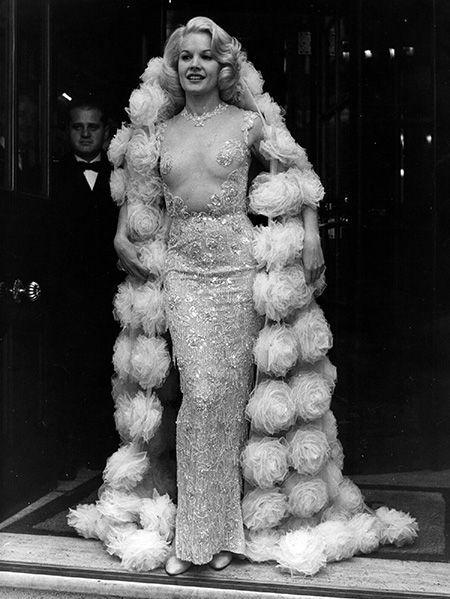 <p>フィギアの衣裳のようにシアーでありながら、大切な部分はゴージャスな刺繍ででカバーするというクチュリエ泣かせなドレスで登場。この時代(1964年)としては、衝撃的なドレスだったのかも?</p>
