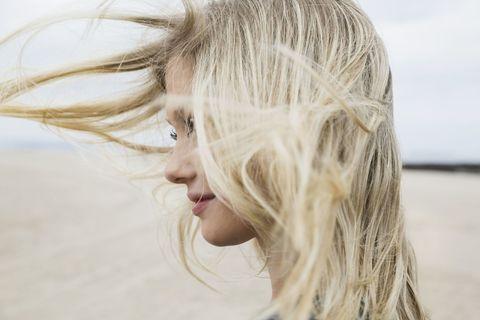 海辺で美髪をなびかせる女性