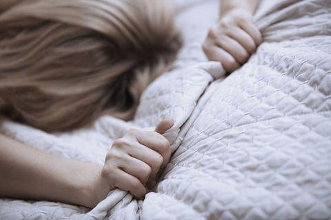 ベッドの上でブランケットを強く握る女性