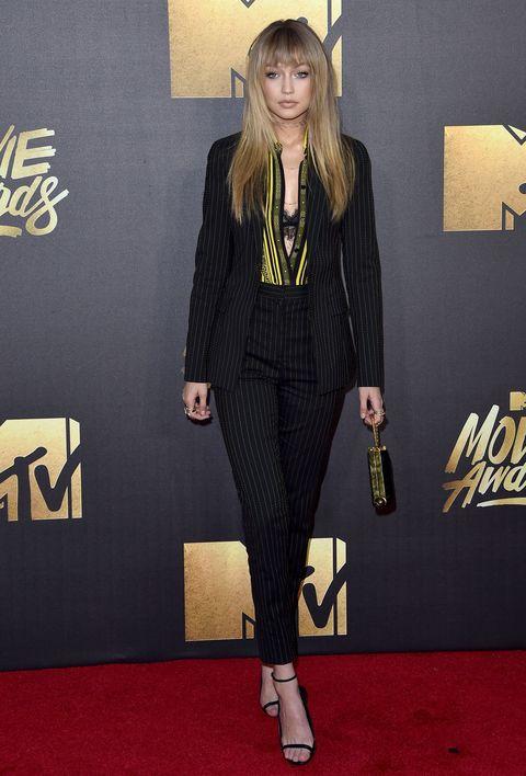 """<p>4月にロサンゼルスで行われた「MTVムービー・アワード」に出席したジジは、「ヴェルサーチ」のピンストライプのパンツスーツを纏って登場。前髪をつくってプチイメチェンしたことや、親友のケンダルとのツーショットが<a href=""""http://people.com/style/mtv-movie-awards-2016-did-gigi-hadid-really-get-bangs/"""" data-tracking-id=""""recirc-text-link"""" target=""""_blank"""">話題</a>に。</p>"""