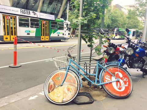"""<p>メルボルンでの移動で外せないのが、写真後ろに見える、この街のシンボルでもあるトラム。観光スポットが集中している市内の中心部は、ほとんどが「フリートラムゾーン」として、無料で周遊できるので便利! 加えて、ヘルメットをつけて自転車で移動をしている人も多い。レンタルサイクルを借りて、サイクリングをするのも気持ちよさそう(オーストラリアにはハエがいっぱい飛んでいるので、目や口に入らないように注意!)。<span data-redactor-tag=""""span"""" data-verified=""""redactor""""></span></p>"""