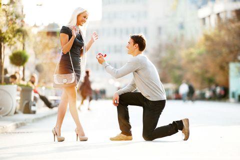 プロポーズで膝ついてる男性と喜ぶ女性