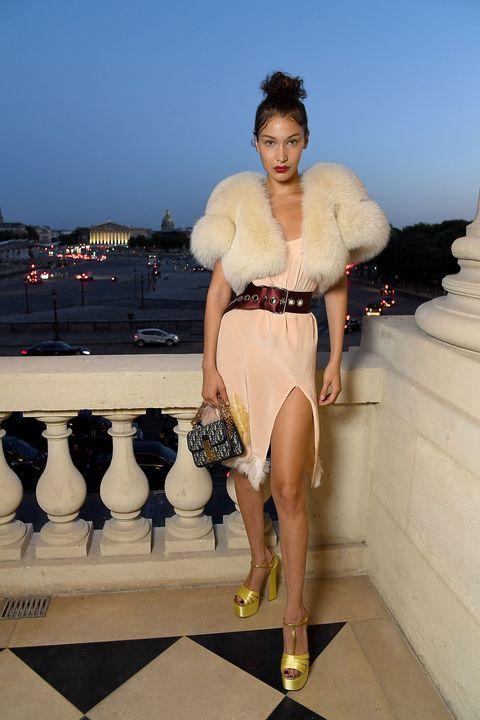<p>パリでおこなわれたミュウミュウのショーでは、フェザーでトリミングされたセクシーなピーチカラーのスリップドレスをチョイス。ボルドーの太ベルトでシックに引き締めながら、ファージャケットでグラマラスに味付け。小ぶりなディオールのロゴバッグをワンポイントに。</p>