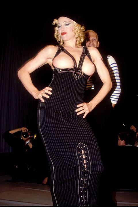 """<p>1992年に開催されたエイズのためのチャリティファッションショー。ランウェイに登場したマドンナはジャケットのようなものを羽織っていたけど、途中でそれを脱ぎ胸を露わに。ちなみに、ファッションショーでは70万ドル(約7800万円)の<a href=""""http://www.anothermag.com/fashion-beauty/7543/jean-paul-gaultiers-1992-amfar-extravaganza"""" target=""""_blank"""" data-tracking-id=""""recirc-text-link"""">寄付金</a>が集まったそう。</p>"""