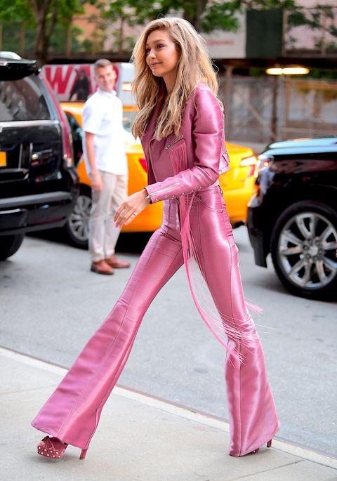 <p>ミレニアル世代のファッションリーダー、ジジはバービーみたいなピンクコーデを披露。フリンジやハトメ使いにロックスピリットが弾けるバイカージャケットと美脚をこれでもかと強調するフレアパンツは、注目ブランド、クリストのもの。ソールにパールがついたアクアズーラのベルベットサンダルで正真正銘のALLピンク!</p>