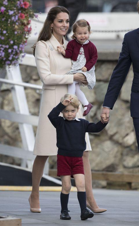 """<p>また別のチルドレンズパーティでは、子ども達はカナダを象徴するメープルになぞらえた""""メープルローズ""""と呼ばれる赤でお揃いに。なんだかご機嫌そうなシャーロット王女と、緊張気味のジョージ王子の後ろで、2人をあたたかく見守るキャサリン妃はまたもオフホワイトコーデ。スッキリとしたデザインながら、端々のディテールが丸み帯びたコートが、無駄のない上品さを演出。さらに胸元にはメープルリーフ型のブローチをさりげなく添えて、お呼ばれコーデとしても隙がない完成度に!</p>"""
