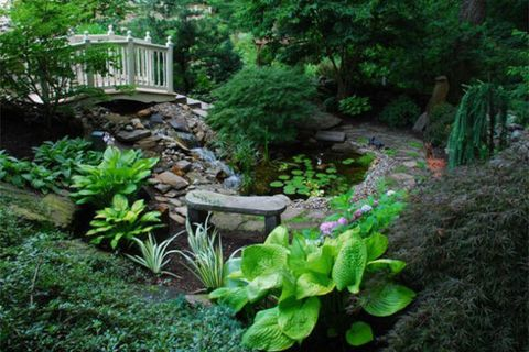 A stone gate opens to two private acres of twisting garden paths dotted with garden sculptures, beds of daylilies, a waterfall surrounded by Japanese maples, and much more.