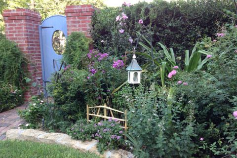 "This gardener took cues from English traditions, and created sectioned-off ""rooms"" on her property. Behind this blue gate, you'll find a butterfly garden.