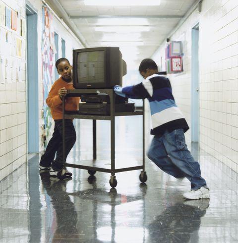 boys pushing TV on a cart