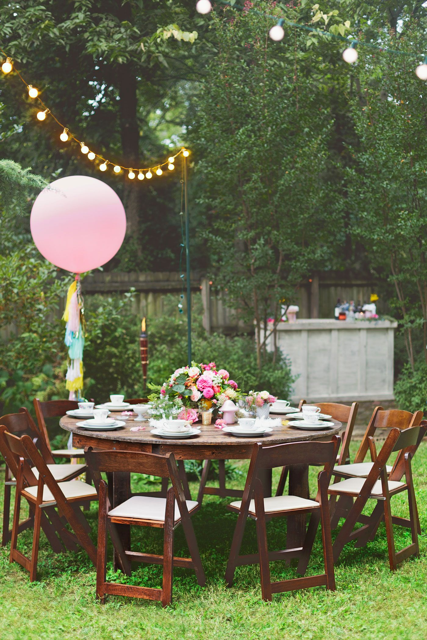 "Kacey's Nashville backyard was transformed into what she describes as an ""Alice in Wonderland-esque garden party"" thanks to twinkling lights, festive garlands and balloons, and a dance floor."