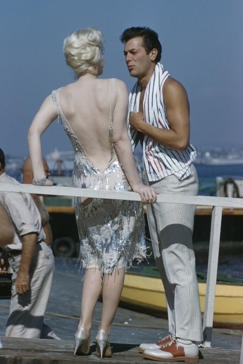 American actors Marilyn Monroe (1926-1962) and Tony Curtis (1925-2010) pictured together on location near San Diego, California during production of the film 'Some Like It Hot' in 1958. Marilyn Monroe and Tony Curtis play the characters of Sugar Kane Kowalczyk and Joe/Josephine in the film. (Photo by Rolls Press/Popperfoto/Getty Images)