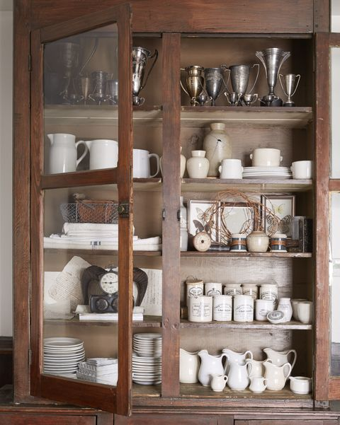 cupboard filled with collections of white ironstone and silver trophies