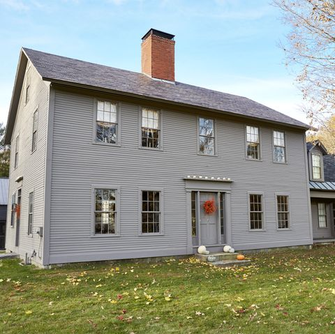gray house with a wreath and pumpkins on the porch