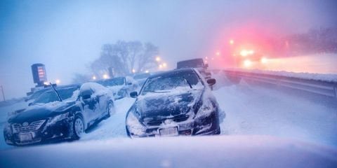 cars stuck on highway in winter snowstorm.
