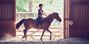 Child horse riding in a sunlit barn