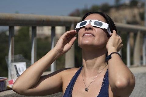 Woman using solar eclipse glasses