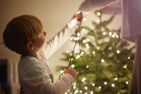 how to hang christmas lights boy stringing lights - Best Way To String Lights On A Christmas Tree