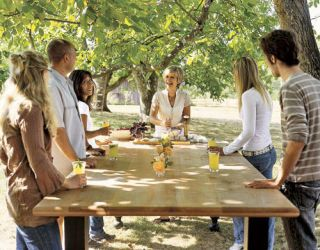group of people standing around a wood table in the woods