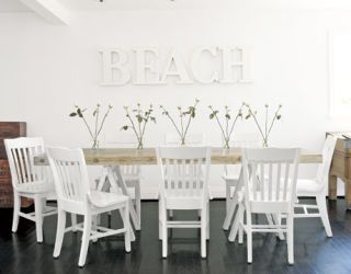 informal dining room with folding chairs and beach in white letters on the wall