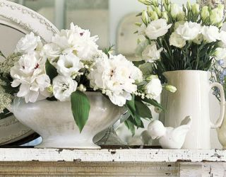 white flowers in white vases with bird figurine