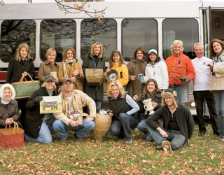 group of people holding flea market purchases in front of a bus