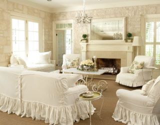 a white living room with chairs and couch covered in slipcovers