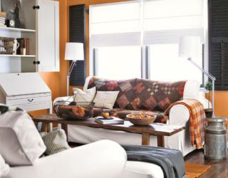 orange family room with white furniture and shelves and patchwork blankets