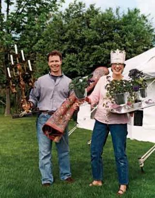 man and woman holding plants and antiques