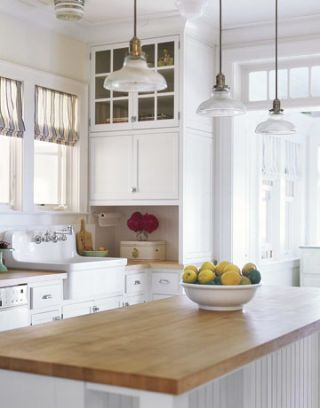 white kitchen with hanging lights and wood top island