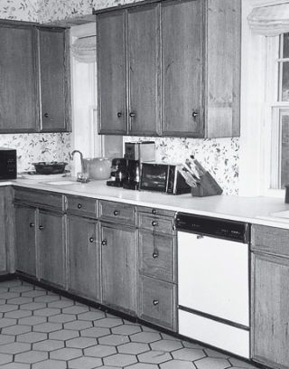 black and white before shot of a kitchen with honeycomb tile and wood cabinets